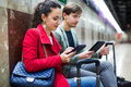 Subway passengers waiting a train reading with modern gadgets as Royalty Free Stock Images