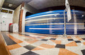 Subway train in motion at the station wide angle view of modern light blue illuminated and spacious public metro marble Stock Images