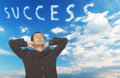 Success clouds handsome young businessman looking up in the sky where spell the word Stock Photos