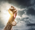 Success male hand rise up a gold medal against the dramatic sky with copy space Stock Photo
