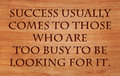 Success usually comes to those who are too busy be looking for it quote by henry david thoreau on wooden red oak background Royalty Free Stock Photos
