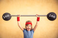 Success and winner concept funny shouting child with barbell girl power feminism sport fitness kid Stock Photos