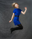 Success young active businesswomen jumping in blue dress studio shot this image has attached release Stock Images
