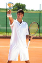 Successes tennis player smiling winner showing his golden goblet Royalty Free Stock Photo