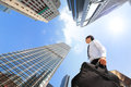 Successful business man outdoors next to office building happy buildings with cityscape and sky hong kong asia asian Royalty Free Stock Photography