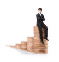 Successful business man sitting on money stairs coin and cross arms with smile isolated against white background asian male model Royalty Free Stock Image