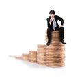 Successful business man sitting on money stairs coin and point to you with smile isolated against white background asian male Royalty Free Stock Photo