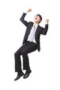 Successful business man sitting on something excited handsome with arms raised and isolated against white background asian male Royalty Free Stock Photos