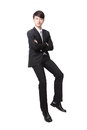 Successful business man sitting on something and look to you isolated against white background asian male model Royalty Free Stock Photography