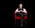 Successful business man in vest and tie sitting in red velvet chair on black background looking intently Royalty Free Stock Image