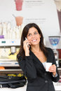 Successful business woman on coffe break cheerful hispanic talking the phone in cafe executive businesswoman or entrepreneur a Stock Image
