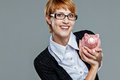 Successful business woman holding a little piggy bank isolated on grey Stock Images