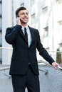 Successful businessman cheerful young man in formalwear talking on the mobile phone while going downstairs Stock Images