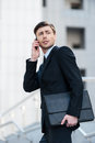 Successful businessman cheerful young man in formalwear talking on the mobile phone and looking away Stock Photography