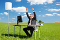 Successful businessman happy raising his arms in a green meadow Stock Images