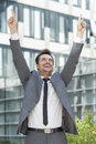 Successful businessman pointing upwards outside office building Royalty Free Stock Photo