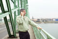 Successful businessman standing on bridge and calling Royalty Free Stock Photo