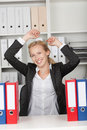 Successful businesswoman with arms raised in office happy thoughtful Royalty Free Stock Image