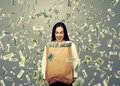 Successful businesswoman with money and smiley holding paper bag under dollar s rain Royalty Free Stock Images