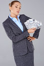 Successful businesswoman with a wad of money displaying fanned out in her hand looking at it speculative look over grey Royalty Free Stock Images