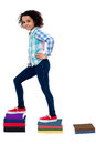 Successful child moving up in school grades smart active girl kid climbing notebooks ladder Royalty Free Stock Photo