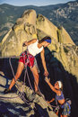 Successful climbing team of female climbers conquer the summit of a challenging rock spire Stock Photos