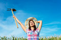 Successful female farmer raising hoe in corn field and smiling countryside blissful woman with work tool wearing straw hat and Royalty Free Stock Images