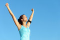 Successful fitness woman with earphones and exercising success sweaty listening music through raising arms to clear blue sky Stock Images