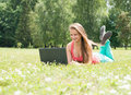 Successful girl online. Beautiful young woman with notebook in the park. Happy student lying on grass with laptop. Outdoor. Royalty Free Stock Photo