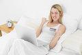 Successful happy woman home shopping with her notebook lying on bed Stock Photography