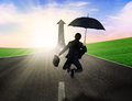 Successful insurance agent happy businesswoman jumping with umbrella on the road Stock Photography