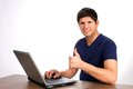 Successful internet transaction young man smiles and gives a thumbs up sign after executing a or purchase on a website from his Stock Photo