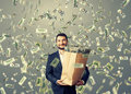 Successful man under dollar s rain and smiley businessman holding paper bag with money Royalty Free Stock Photo
