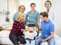 Successful medical team with newborn baby and portrait of parents in hospital room Stock Image