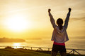 Successful sporty woman with arms up raising towards golden beautiful sunset and sea female athlete celebrating sport success and Stock Photo
