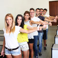 Successful students holding thumbs up in the university Royalty Free Stock Photos