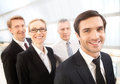 Successful team cheerful young men in formalwear looking at camera and smiling while his colleagues standing behind him Royalty Free Stock Photo
