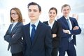 Successful team portrait of young businessman looking at camera with hispartners on background Royalty Free Stock Image