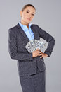 Successful wealthy businesswoman posing with her hand on her hip and a fistful of dollar banknotes Royalty Free Stock Photos