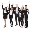 Successful welldressed businesspeople with arms raised full length portrait of standing over white background Royalty Free Stock Image