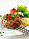 Succulent cooked beef burger with potatoe and salad on a white plate Stock Image