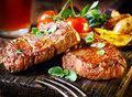 Succulent fillet steak and roast vegetables thick juicy portions of grilled served with tomatoes on an old wooden board Royalty Free Stock Image