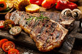 Succulent tender grilled porterhouse steak close up of a seasoned with pepper and rosemary on a wooden board with fresh halved Royalty Free Stock Photo