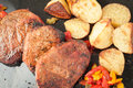 Succulent thick juicy portions of grilled fillet steak served with roasted potatoes and peppers on black granite board Royalty Free Stock Photo