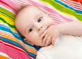 Sucking thumb portrait of a beautiful months baby lying on bed and Stock Photos