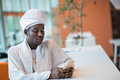 Sudanese business man in traditional outfit using mobile phone in office Royalty Free Stock Photo