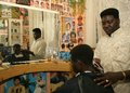 A Sudanese refugee working in a barber shop Royalty Free Stock Photos