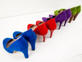 Suede stiletto shoes lined up colourful on teh diagonal on a white floor infront of a white wall Stock Images