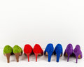Suede stiletto shoes lined up line of colourful on a white floor infront of a white wall Stock Photo