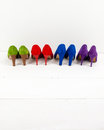 Suede stiletto shoes in a row of colourful on white floor infront of white wall Royalty Free Stock Photo